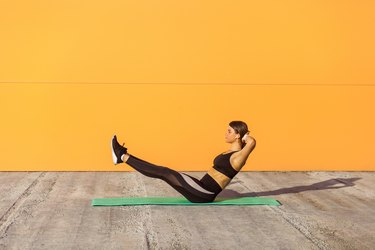 Young sporty attractive woman practicing yoga, doing paripurna navasana exercise, balance pose, working out, wearing sportswear, black pants and top.