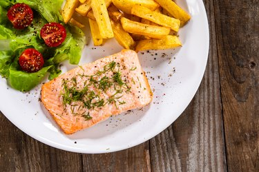 Grilled salmon with French fries and vegetable salad