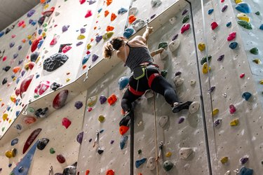 Woman climbing an indoor rock climbing wall