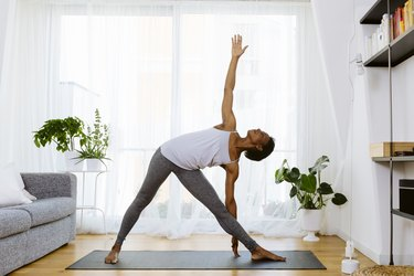 woman practicing Vinyasa yoga at home
