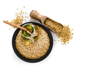 Flax seed oil and flax seeds shot from above on white background