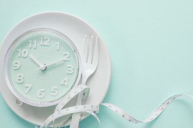 Blue clock on white plate, Intermittent fasting concept, ketogenic diet, weight loss, skip meal