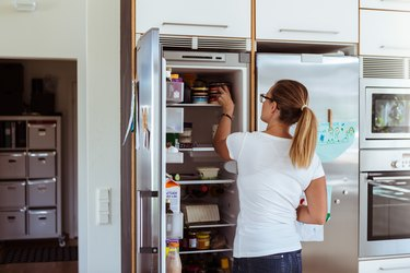 woman storing canned food in fridge