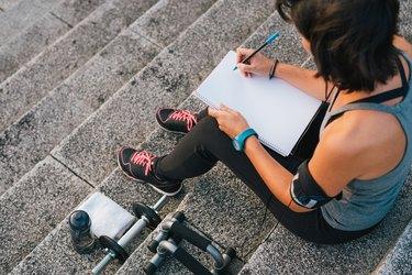 Urban female athlete focusing on her goals writting on notepad