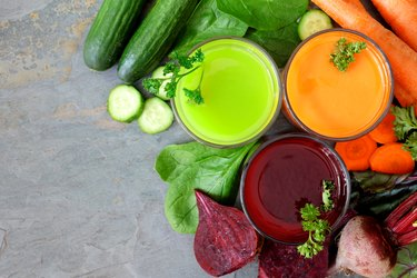 Three types of healthy vegetable juice, above view on slate