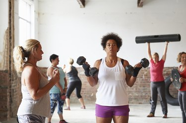 Female fitness trainer instructing woman lifting dumbbells