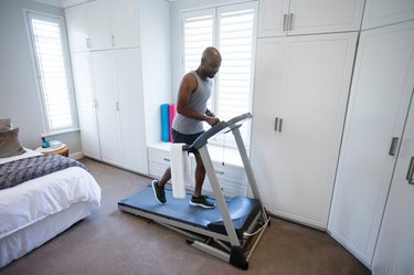 Mid section of man using smart watch while exercising on treadmill