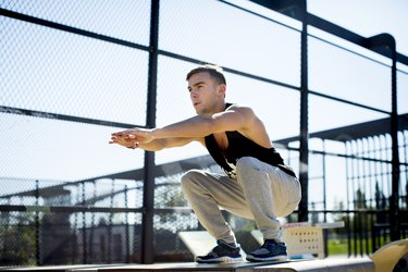 Young man squatting outdoors