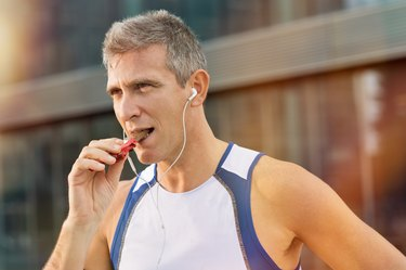 Fitness Man Eating Protein bar