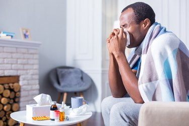 Adult man sneezing because he has the flu