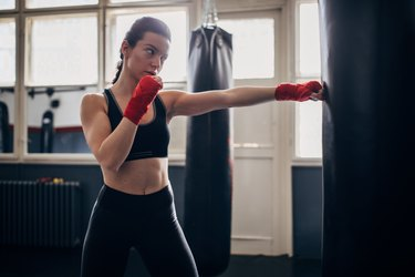 Woman wearing boxing wraps and punching a bag at the gym