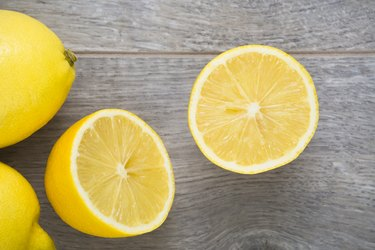Ripe, yellow, halved lemon fruit on wooden texture table. Directly above view.