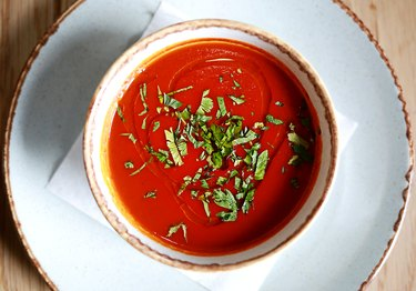 Tomato and basil soup on a white plate compatible with low-carb diet