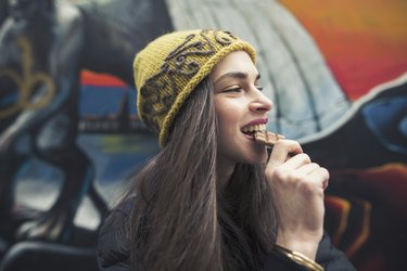 Image of a young woman biting a chocolate bar