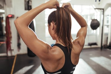 Woman showing off strong, big arms and tying her hair in a ponytail at the gym