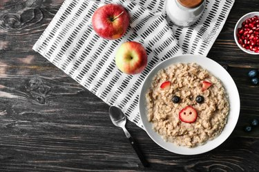 Plate with creative oatmeal for children on dark wooden table