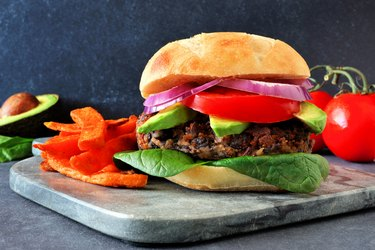 Veggie burger with sweet potato fries on a dark background