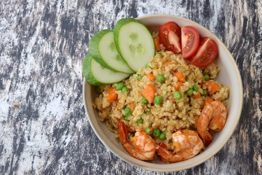 Nasi Goreng Udang. Indonesian fried rice with prawns, egg, pea, carrot, tomato and cucumber