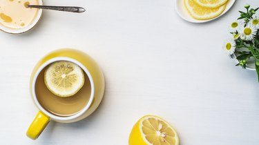 Flat lay of lemon tea in a yellow cup, honey, half a lemon and chamomile on a white background