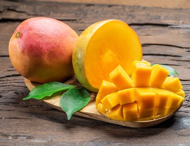 Mango fruits and mango slices on a wooden table