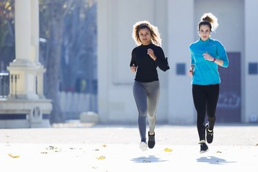 Two focused young women running listening to music