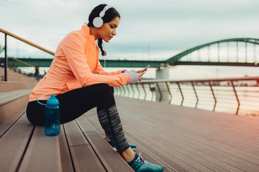 woman taking a break after jogging to drink and track water