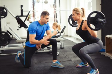 Young woman lifting barbell with her personal trainer motivation.