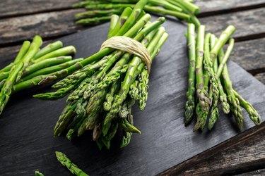 Fresh raw green Asparagus on wooden chopping board