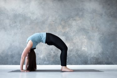 Woman practicing yoga, standing in Urdhva Dhanurasana pose