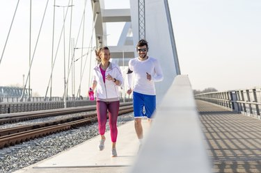 Couple jogging at the bridge with headphones