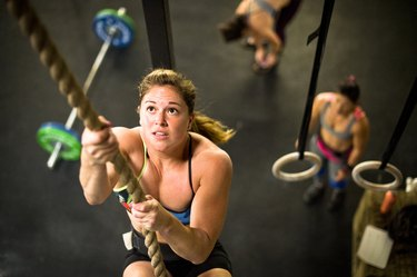 Female athlete performing rope climbing in CrossFit gym