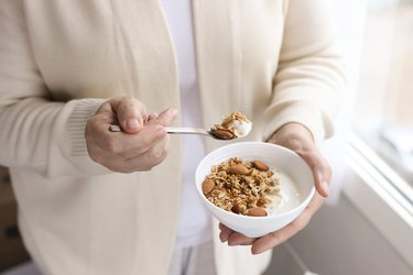 An unrecognizable woman eating a bowl of yogurt with granola and almonds on top