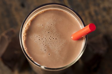 Top view of a chocolate protein shake in a glass with a straw