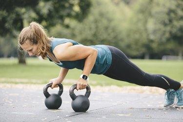 Young woman going pushups on kettlebells