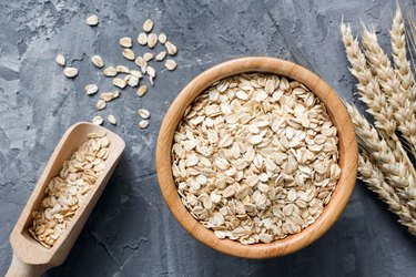 Rolled oats or oat flakes in wooden bowl on stone background.