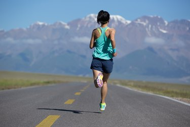 Rear view of fitness woman runner running on road