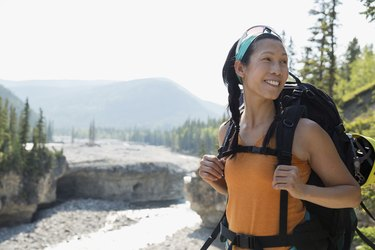 Woman backpacking above river, going on a long-distance walk