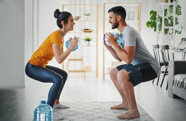 Couple working out at home with a jug of water