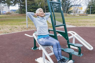 Mature Woman with Grey Hair Exercising at Outdoor Gym