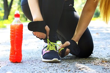 A female athlete tying her shoe with a sports drink next to her