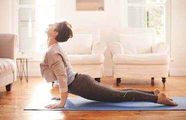 older woman does a prone press up on a yoga mat at home