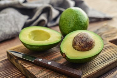 Fresh avocado on a wooden cutting board