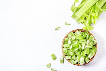 Fresh green celery chopped pieces in bowl, white background, top view, copy space