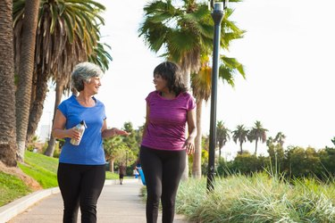 Female friends walking in park for exercise, holding water bottles
