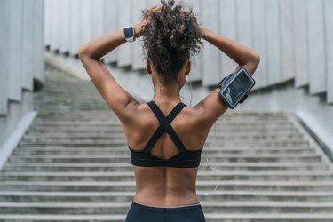 Rear view of woman runner tying her hair and getting ready for another run outdoors
