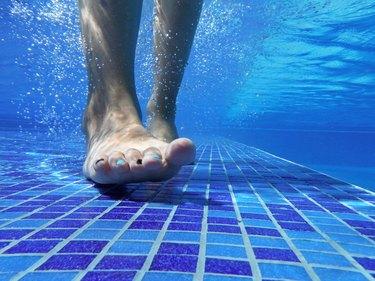 Underwater shot of feet on pool bottom