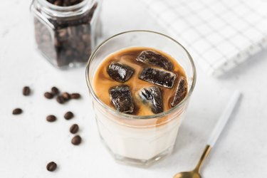 Iced coffee with milk on concrete background
