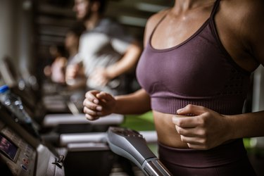Unrecognizable athletic woman running on treadmill during sports training in a gym.