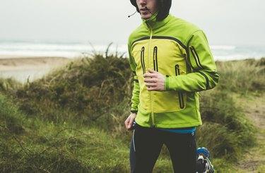 Man running in the rain on the beach