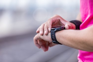 runner outside looking at heart rate monitor smartwatch